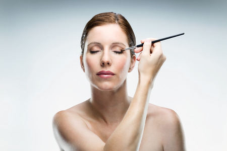 Portrait of beautiful young woman applying make up over white background. 스톡 콘텐츠