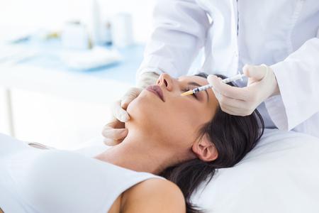 Retrato de mujer joven hermosa recibiendo inyección cosmética de botox en su rostro.