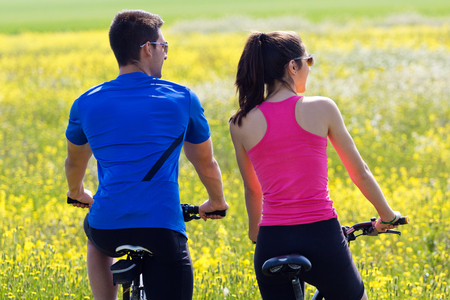 Spring portrait of  Happy young  couple on a bike ride in the countryside