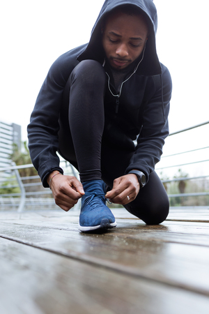 Portrait of fit and sporty young man tying her laces before a run in the city.