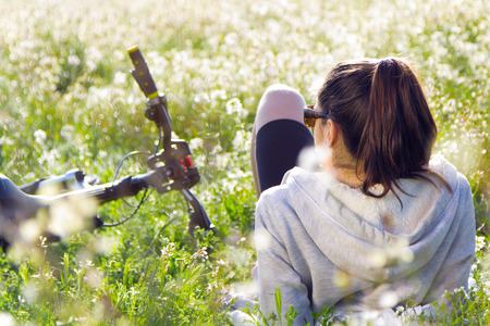 Spring portrait of young woman with mountain bike stretched on the field and watching the horizon