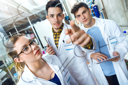 Portrait of young scientists carrying out an experiment in a laboratory.