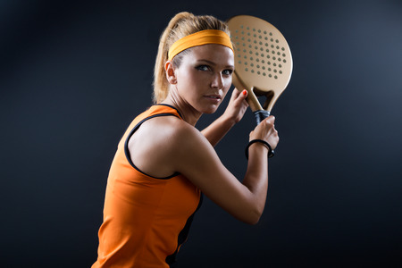 Portrait of beautiful woman playing padel indoor. Isolated on black.