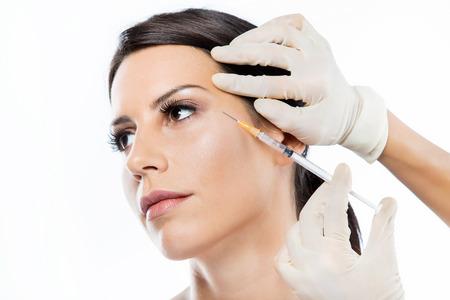Portret piękna młoda kobieta dostaje zastrzyk kosmetyczny z botoksu w twarz na białym tle.