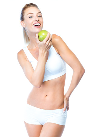 Portrait of beautiful young woman eating an apple over white background. Stock fotó