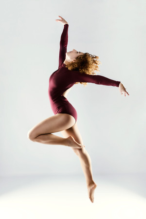 Portrait of beautiful young professional dancer dancing over white background. Banque d'images