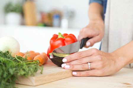 Close-up of hands of young woman cutting fresh vegatebles in the kitchen. Banco de Imagens