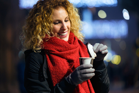 Portrait of beautiful young woman drinking coffee in the street at night.