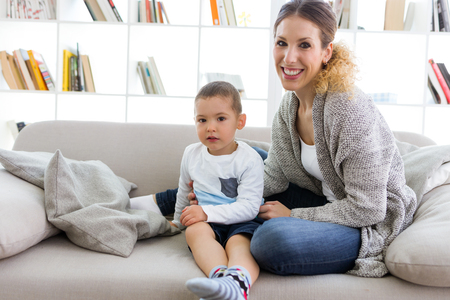 Portrait of beautiful young mother and her son looking at camera at home.
