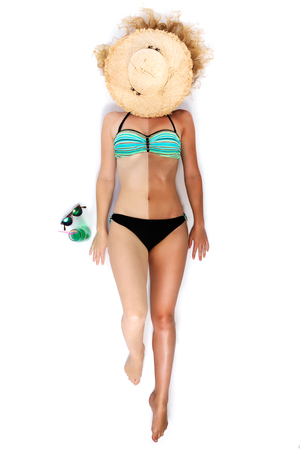 Shot of young attractive woman in bikini sunbathing on the white floor. Stock Photo