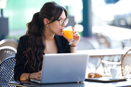Shot of beautiful young woman drinking orange juice while working with her laptop in a coffee shop.