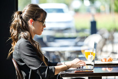 Shot of beautiful young woman working with her laptop while having breakfast in a coffee shop.