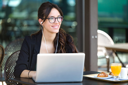 Shot of beautiful young woman looking sideways while working with her laptop in a coffee shop.