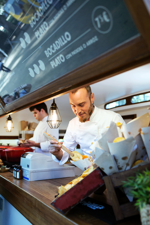 Portrait of young chef serving barbecue potatoes in a food truck. Banco de Imagens