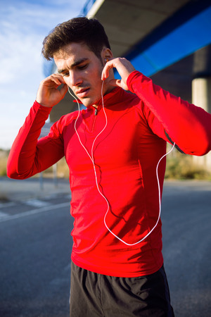 Portrait of sporty young man listening to music in the street. Stockfoto