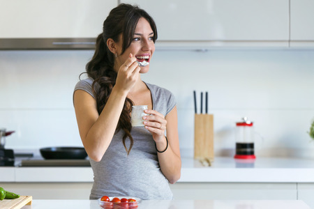 Shot of beautiful young woman eating yogurt in the kitchen at home. Looking sideway.
