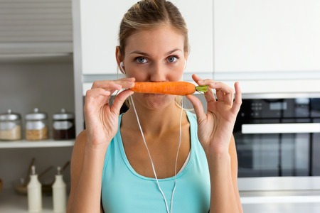 Portrait of beautiful young sporty woman playing with carrot while listening to music with earphones in the kitchen. Stock Photo