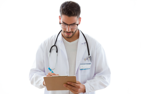 Shot of attractive young male doctor with stethoscope over neck taking notes in clipboard isolated on white background.