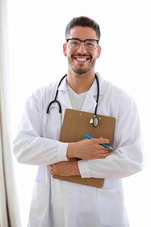 Portrait of attractive young male doctor with stethoscope over neck holding clipboard isolated on white background. Archivio Fotografico