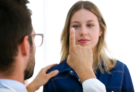Shot of attractive male doctor ophtalmologist checking the eye vision of beautiful young woman in modern clinic. Stockfoto