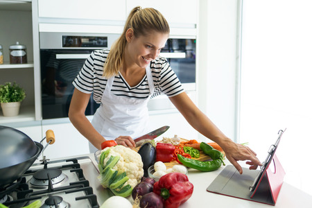 Shot of healthy young woman cutting fresh vegetables and using digital tablet to recipes in the kitchen at home. 스톡 콘텐츠