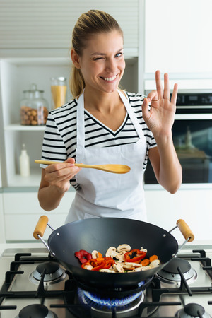 Portrait of healthy young woman looking at camera while cooking and mixing food in frying pan in the kitchen at home. Banco de Imagens