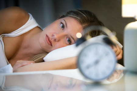 Shot of beautiful young exhausted woman suffering insomnia lying on bed in bedroom at home. Фото со стока