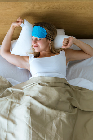 Shot of pretty young woman pulling up sleeping mask and stretching after wake up in the bedroom at home.