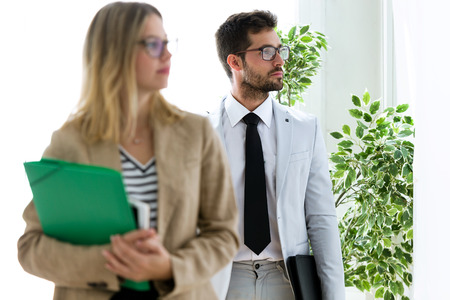 Shot of attractive young business partners looking sideways in a hallway of they company.