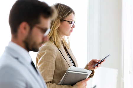 Shot of two attractive young business partners texting with their smartphones in a hallway of they company.