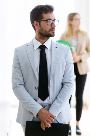 Shot of handsome young businessman looking sideways with his partner behind in a hallway of they company.