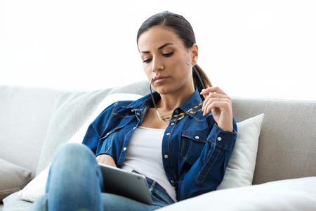 Shot of confident young woman with eyeglasses working with digital tablet on sofa at home. Stock Photo