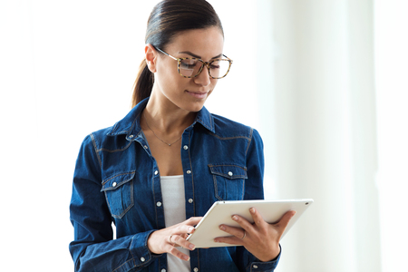 Shot of beautiful young woman with eyeglasses working with digital tablet over white backgound. Imagens