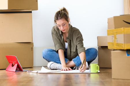 Shot of pretty young woman drawing blueprints of her new house while sitting on the floor at home. Фото со стока