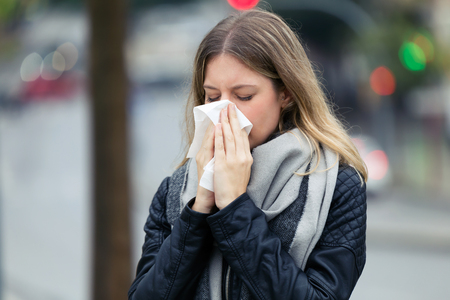 Shot of illness young woman sneezing in a tissue in the street. Stock Photo