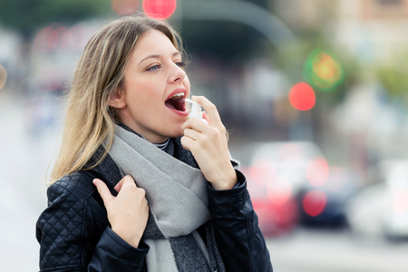 Shot of illness young woman using a analgesic spray to soften the throat in the street. Stockfoto