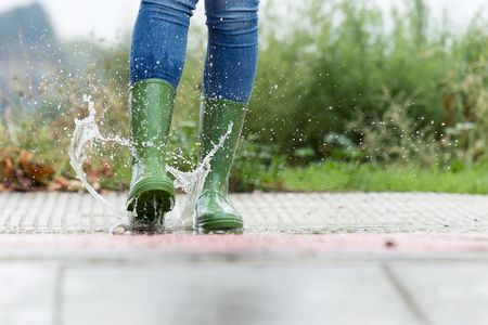 Close-up of woman in green rubber boots jumping on the puddle water in the street. 免版税图像 - 113272323