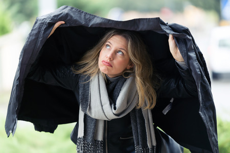 Shot of beautiful young worried woman covering herself with her jacket because its raining in the street. Stok Fotoğraf