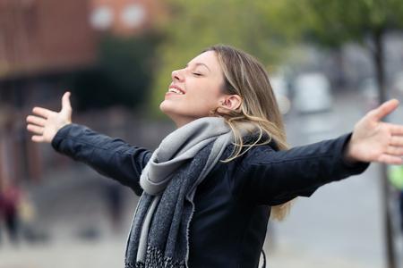 Foto de sonriente joven respirando aire fresco y levantando los brazos en la ciudad.