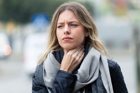 Strzał choroby młoda kobieta z okropnym bólem gardła idąc na ulicę. Zdjęcie Seryjne