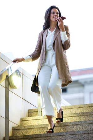 Shot of fashion young beautiful businesswoman talking with her smartphone in the street.