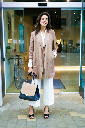Portrait of stylish young beautiful businesswoman posing in the street outside the coffee shop. Banco de Imagens