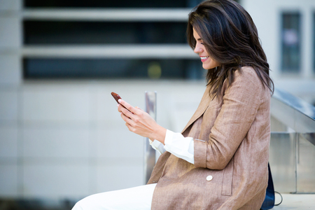 Shot of beautiful young businesswoman texting with her mobile phone in the street. Banco de Imagens
