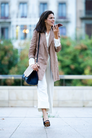 Shot of fashion young beautiful businesswoman talking with her mobile phone in the street.