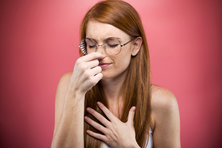 Shot of redhead young woman pinching her nose over pink background.