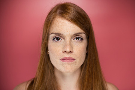 Portrait of redhead young serious woman looking at camera over pink background. Banco de Imagens