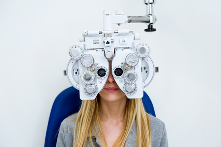 Shot of pretty young woman doing eyesight measurement with optical phoropter in ophthalmology clinic. Stockfoto