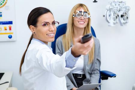 Aufnahme einer Optikerin mit einem Proberahmen, der die Sicht des Patienten in der Augenklinik überprüft. Selektiver Fokus auf Arzt. Standard-Bild