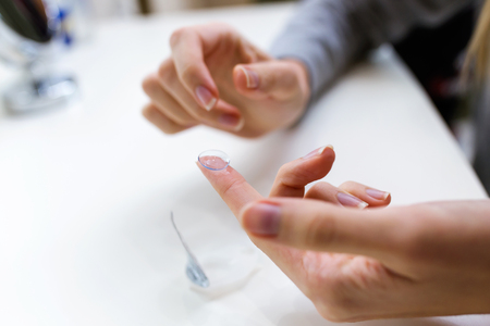 Close-up of hands of young woman holding one contact lenses before putting on them. Фото со стока