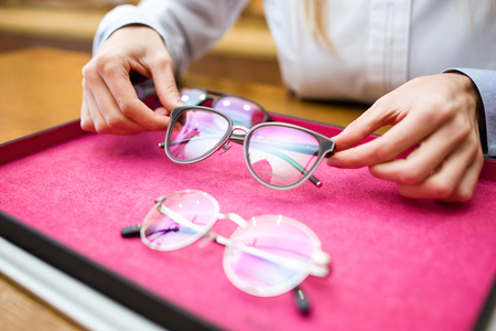 Close-up of ophthalmologist hands showing eyeglasses to customer in optic shop.